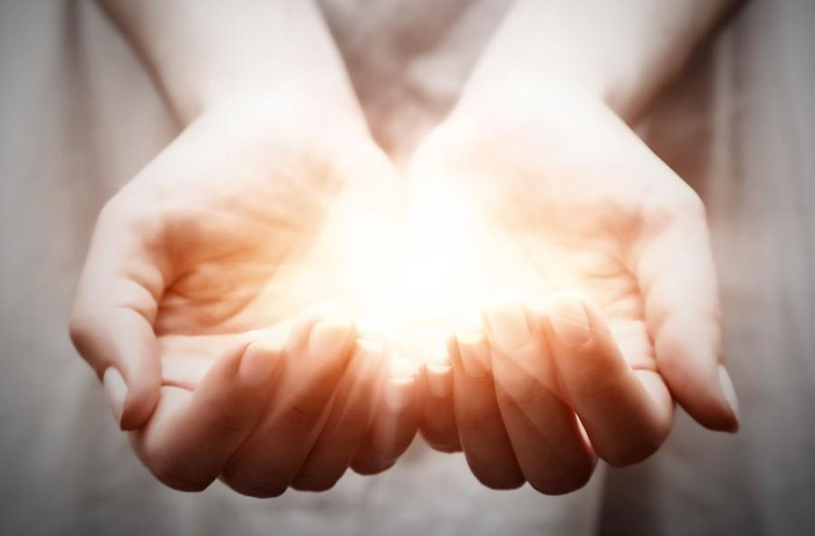 The light in young woman hands. Sharing, giving, offering, prote